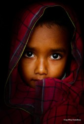 I found him in a fishermen's village at Gabura in Bangladesh. He was covering his head with a cotton towel while looking at me in awe. When I turned to him, he got a little shy. His innocent look drew me towards him.