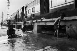 Street children bathing at the Washing Line, New Delhi Railway Station.