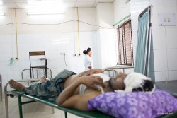 : A man lying in the casualty department of a medical college hospital with a severe head injury.